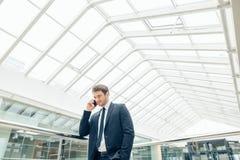 Бизнесмен идя пока говорящ на мобильном телефоне на его пути работать Стоковая Фотография
