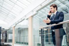 Бизнесмен идя пока говорящ на мобильном телефоне на его пути работать Стоковые Изображения