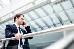 Бизнесмен идя пока говорящ на мобильном телефоне на его пути работать Стоковые Фото