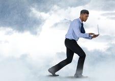 Бизнесмен идя с компьтер-книжкой в облачном небе Стоковое Изображение RF