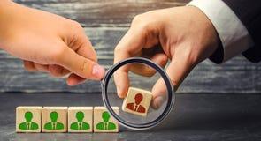Бизнесмен извлекает/увольняет работника от команды управление внутри команда деревянные блоки с изображением  стоковая фотография