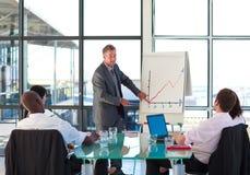 бизнесмен изображает диаграммой старший отчетности к Стоковые Фотографии RF