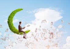 Бизнесмен или студент сидя на зеленой луне и посылают сообщение с smartphone Стоковая Фотография