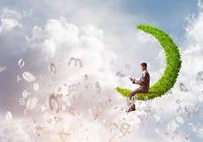Бизнесмен или студент сидя на зеленой луне и посылают wi сообщения Стоковая Фотография RF