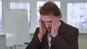 Бизнесмен имеет головную боль на офисе стоковое изображение