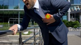 Бизнесмен имеет сердечный приступ outdoors, пятно показывает боль в комоде, скорой помощи стоковое фото