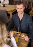 Бизнесмен имея еду с женским коллегой внутри стоковые фотографии rf