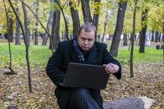 Бизнесмен имея компьтер-книжку в парке осенью Молодой человек сидя на дереве в парке с компьтер-книжкой на его подоле и электронн Стоковое фото RF