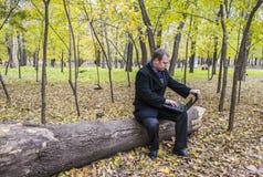 Бизнесмен имея компьтер-книжку в парке осенью Человек работает на компьютере в парке Стоковая Фотография