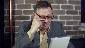 Бизнесмен использует цифровую таблетку в комнате с кирпичной стеной видеоматериал