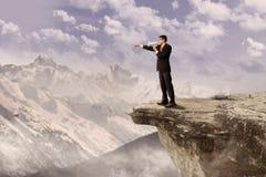 Бизнесмен используя диктора на скале Стоковое фото RF
