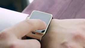 Бизнесмен используя его smartwatch app около деревянной предпосылки таблицы, новой технологии акции видеоматериалы