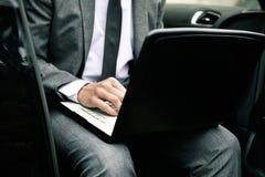Бизнесмен используя компьтер-книжку в автомобиле стоковые изображения