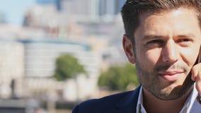 Бизнесмен используя мобильный телефон с горизонтом города в предпосылке видеоматериал