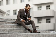 Бизнесмен используя мобильный телефон app отправляя СМС вне офиса в городском городе с зданиями небоскребов на заднем плане Стоковое фото RF