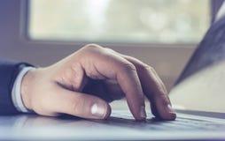 Бизнесмен используя портативный компьютер Мужская рука печатая на клавиатуре компьтер-книжки стоковое фото