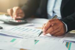 бизнесмен используя ручку и калькулятор работая в офисе Финансы стоковые изображения