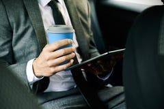 Бизнесмен используя таблетку в автомобиле стоковые фото