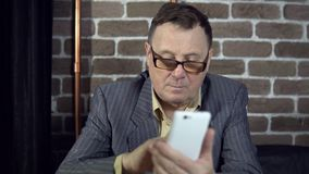 Бизнесмен используя телефон в комнате с кирпичной стеной сток-видео