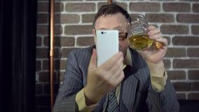 Бизнесмен используя телефон и выпивая спирт внутри помещения с кирпичной стеной акции видеоматериалы