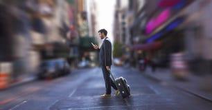 Бизнесмен используя телефон и держащ чемодан против предпосылки города Стоковое Изображение RF