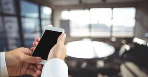 Бизнесмен используя телефон против предпосылки офиса Стоковые Фотографии RF