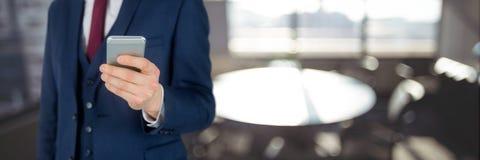 Бизнесмен используя телефон против предпосылки офиса Стоковое Фото