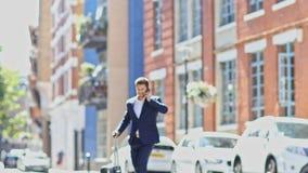 Бизнесмен используя улицу города скрещивания мобильного телефона с чемоданом сток-видео