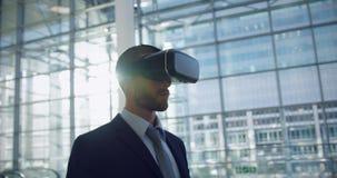 Бизнесмен используя шлемофон виртуальной реальности в лобби на офисе 4k сток-видео