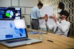 Бизнесмен используя шлемофон виртуальной реальности пока коллеги обсуждая над диаграммой сальто Стоковые Изображения