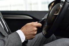 Бизнесмен используя smartphone в автомобиле стоковые изображения rf