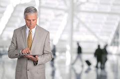 Бизнесмен используя авиапорт планшета Стоковые Изображения