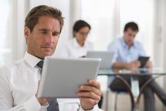 Бизнесмен используя его таблетку в офисе Стоковое фото RF