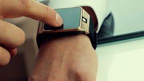 Бизнесмен используя его smartwatch app в офисе видеоматериал