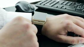Бизнесмен используя его smartwatch app около предпосылки клавиатуры и мыши, новой технологии видеоматериал