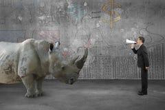 Бизнесмен используя диктора против носорога с стеной doodles Стоковое Фото