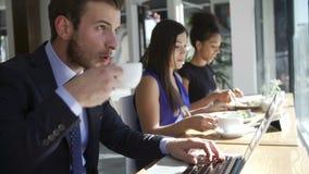 Бизнесмен используя компьтер-книжку в кофейне видеоматериал
