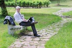 Бизнесмен используя компьтер-книжку в парке Стоковые Фото