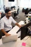Бизнесмен используя компьтер-книжку и настольный ПК совместно Стоковая Фотография RF