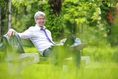 Бизнесмен используя компьтер-книжку и сидеть на стенде Стоковые Изображения