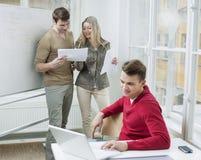 Бизнесмен используя компьтер-книжку пока сотрудники обсуждая над документами в офисе Стоковое Изображение RF