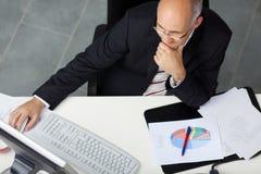 Бизнесмен используя компьютер на столе офиса Стоковые Изображения RF