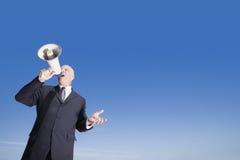 Бизнесмен используя мегафон против голубого неба Стоковые Фото