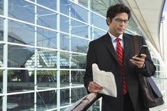 Бизнесмен используя мобильный телефон вне офиса Стоковое фото RF