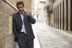 Бизнесмен используя мобильный телефон в улице стоковое изображение