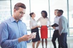 Бизнесмен используя мобильный телефон при коллеги обсуждая в предпосылке Стоковая Фотография