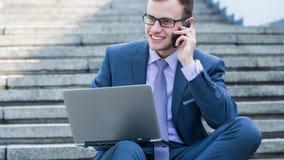 Бизнесмен используя ПК и мобильный телефон компьтер-книжки. Он сидит на лестницы. Стоковые Фото