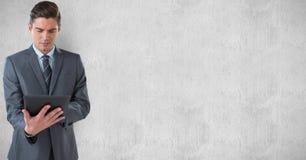 Бизнесмен используя ПК таблетки против стены Стоковая Фотография RF