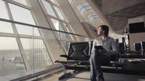 Бизнесмен используя планшет на авиапорте силуэт путешественника человека с рюкзаком Дело и перемещение видеоматериал