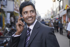 Бизнесмен используя сотовый телефон на улице города Стоковая Фотография